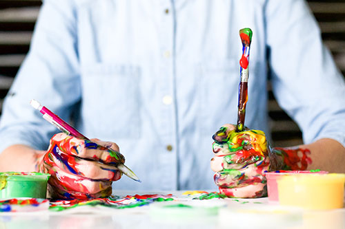 man with colorful paint on his hands while drawing