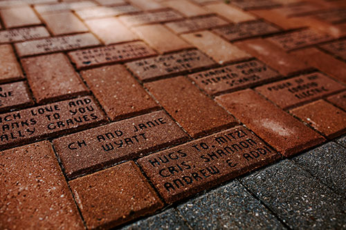 bricks on a sidewalk with names etched in them at Edmond Fine Arts