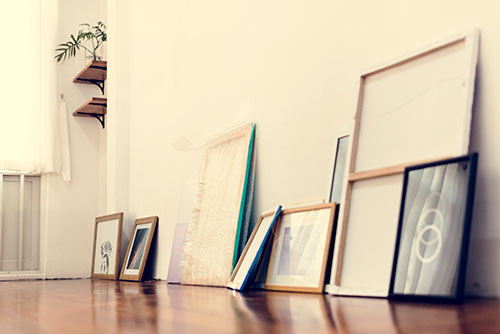 framed works of art sitting against a wall